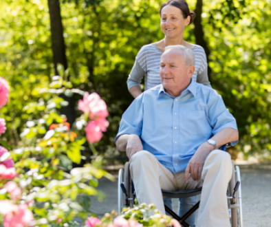 A caregiver enjoying a walk with their loved one in a wheelchair.