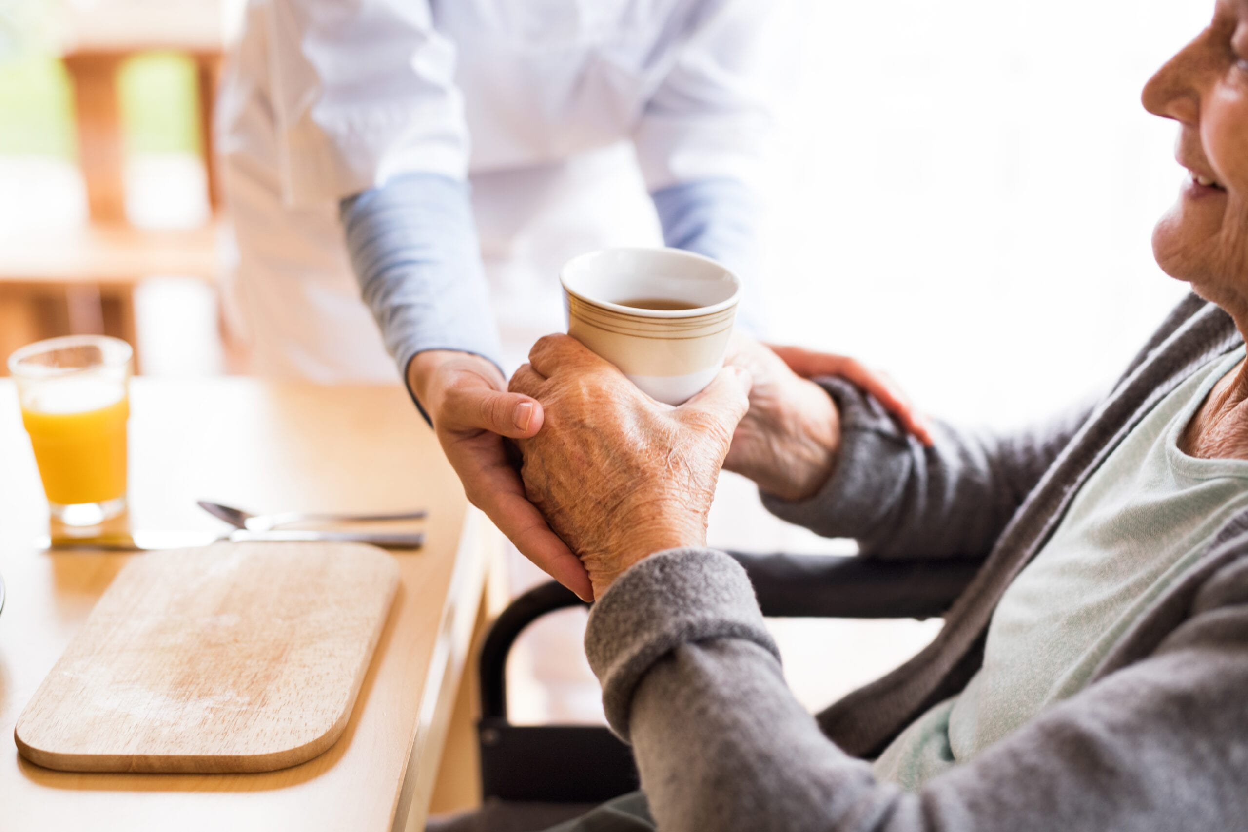 Caregiver assisting an elderly person with a cup of coffee