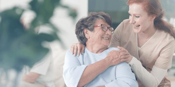 Caregiver with her arm on older woman's shoulder
