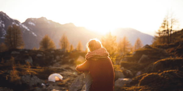 Woman sitting outside amongst trees and rocks watching the sun rise