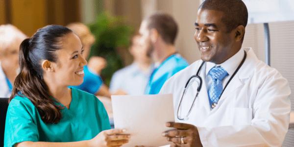 Doctor handing a nurse some nursing paperwork