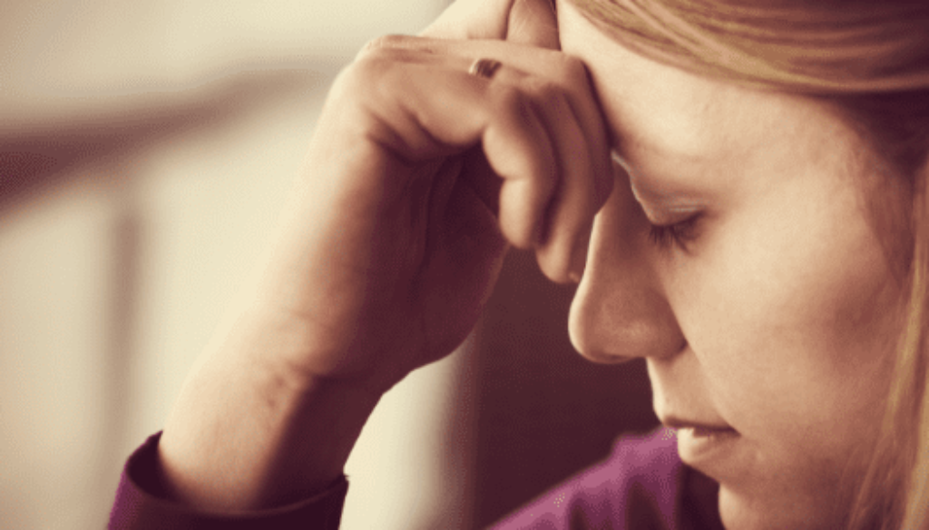 Woman with a hand on her forehead with caregiver guilt
